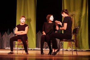 Scena spektaklu pt.: Rekrut - trzy dziewczyny siedzą na krzesłach, dwie z nich zwrócone do siebie twarzą uśmiechają się do siebie trzymając się za ręce, trzecia w niewielkim oddaleniu patrzy z żalem na pozostałą dwójkę