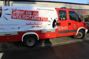 na zdjęciu widać wóz ochotniczej straży pożarnej z przypiętym z boku pojazdu dużym banerem promującym kampanię: zapal się do wolontariatu - wolontariat ma sens!