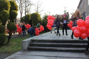 grupa młodzieży idąca dwójkami w kierunku Ośrodka Kultury w Brzeszczach trzymając naręcza czerwonych balonów
