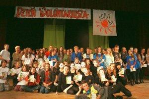 Grupowe zdjęcie wolontariuszy z odebranymi dyplomami, członków teatru TEŻ i koordynatorów wolontariatu. W środku grupy stoi Dyrektor Ośrodka Pomocy Społecznej w Brzeszczach - Elżbieta Krzak oraz Dyrektor Ośrodka Kultury w Brzeszczach - Magdalena Armata