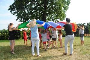 grupa dorosłych trzymająca kolorową okrągłą chustę animacyjną pod którą przebiegają dzieci