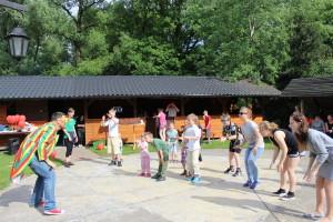 Grupa dzieci i wolontariuszy pod kierunkiem animatora przebranego w strój w kolorowe pasy i duże okulary tańczy taniec integracyjny, klaszczą w dłonie i uda