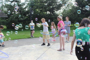 Grupa dzieci kręci kołami hula – hop wśród baniek mydlanych unoszących się w powietrzu